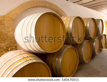 wine wooden oak barrels stacked in a row at Mediterranean winery