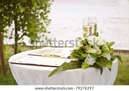 Wineglass,flowers and register book on the table