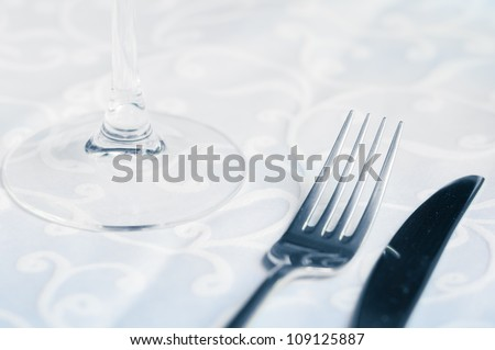Wineglass, fork and knife on the table. Close up.
