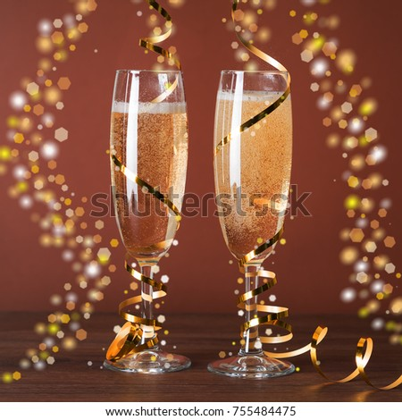 wineglass of champagne and christmas decorations on a brown background square