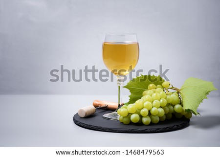 Wineglass of white wine with grape, cork and corkscrew on gray background. Holiday celebration concept #1468479563