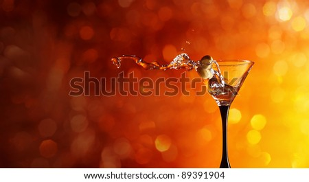 wineglass with martini and green olives. - stock photo