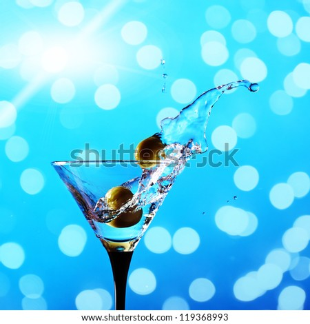 wineglass with martini and green olives on a blue background