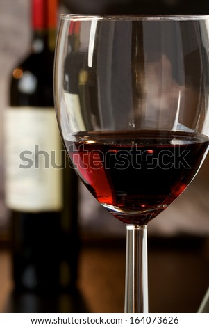 Wineglass with red wine and a bottle in the background