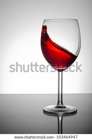 Wineglass with red wine splashing