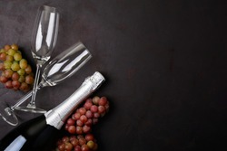 Wineglasses, grapes and bottle of champagne lying on black wooden background. New Year celebration concept. Top view. Flat lay.
