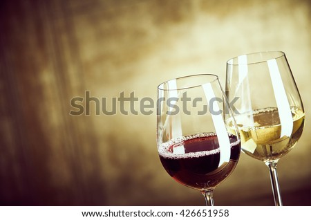 Wineglasses of red and white wine standing side by side in the corner over an abstract rustic brown background with copy space #426651958