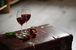 wineglasses with red wine decorated with strawberry and mint.