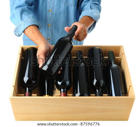 Winemaker standing behind a case of red wine holding one bottle in his hands over the open box. Square format over a white background
