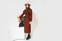 Winer fashion look. Stylish brunette model in brown coat  and beige hat posing in studio on white background. Full lenght. Copyspace fo text.
