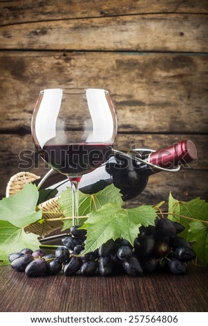 Winery background. Wineglass with bottle of red wine and cluster of grape on wooden table