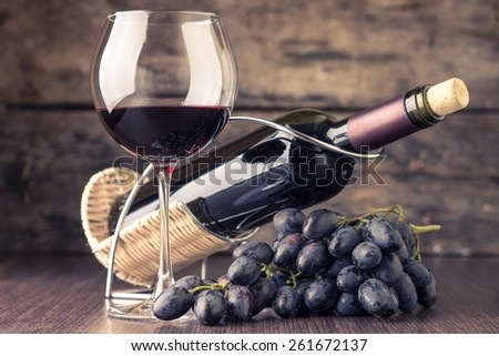 Winery background. Wineglass with bottle of red wine and cluster of grape on wooden table. Toned image
