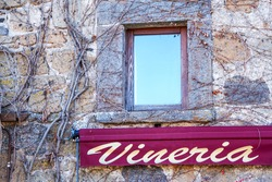 winery sign on an old brick wall , Italy