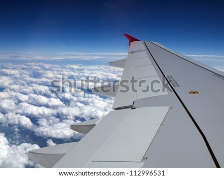 Wing of airplane - flight over white clouds.