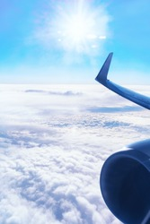 Wing of an aircraft and horizon with blue sky and clouds.