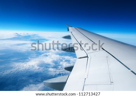 Wing of an airplane flying above the clouds people looks at the sky from the window of the plane using air transport to travel