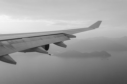 Wing of an airplane flying above the sea near Hong Kong