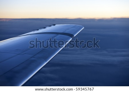 wing of an airplane seconds after sunset