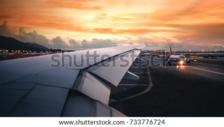 Wing of an airplane taking off on run way in terminal with clouds at sunset, blank copy space