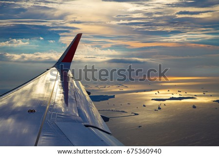 Wing of the plane at landing, beautiful sunset, view from the plane's window, at the bottom of the sea. #675360940