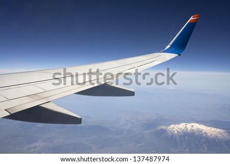 Wing of the plane on blue sky background and snowy mountains below, view from window of a jet plane wing with beautiful weather.