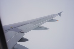Wing surface equipped with aircraft flaps, spoilers (control surfaces) and winglet, at the right side of an airplane flying through thick clouds at high altitude, seen from the porthole of the plane