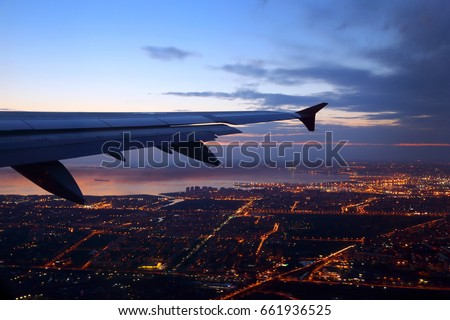 Wing view of civil passenger aiplane taking off at dusk with night city lights seen below. Foto stock ©