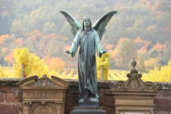 Winged angel standing guard in cemetery with landscape of vineyards, Germany.