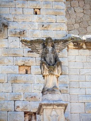 Winged angel statue on aged church facade with a stone background. Religious and spiritual sculpture. Angel decoration on chapel with wings and worship sign.