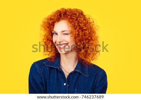 Winking. Closeup woman redhead curly hair smiling blinking eye to you camera isolated on yellow background. Happy life pictures, happiness