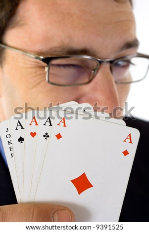 Winking man showing four aces and joker cards in foreground.