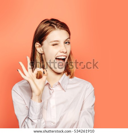 Winking pretty girl young beautiful cute woman female model with red hair in white shirt shows ok gesture on orange background