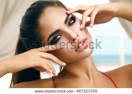 Winking sensual model Girl touching her face,manicure nails,beauty teen face isolated on white background.Joyful young fashion woman with bright make up,red lips and nails,make-up artist,model face