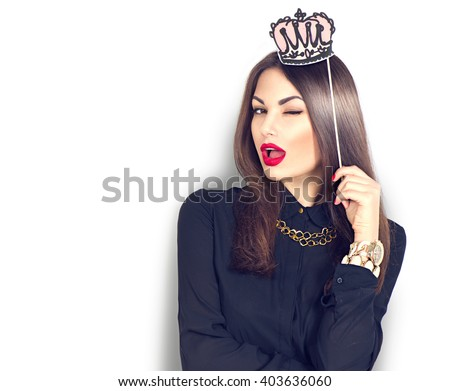 Stock Photo Winking sexy model Girl holding funny paper crown on stick isolated on white background. Joyful young fashion woman with bright make up, red lips and nails