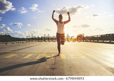 Winner as style of life. Horizontal shot of young beautiful woman in sports clothing keeping arms raised and smiling while passing finish line during jogging. Evening sunlight on background. #679844893