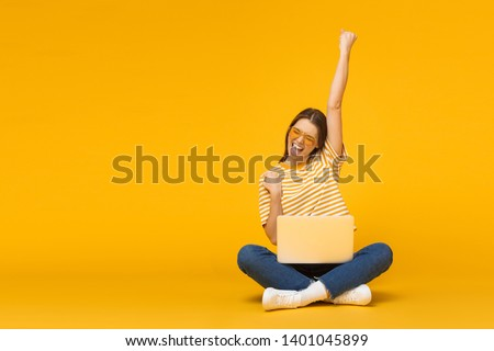 Winner! Excited smiling girl sitting on floor with laptop, raising one hand in the air is she wins, isolated on yellow background