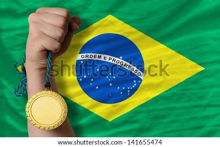 Winner holding gold medal for sport and national flag of brazil