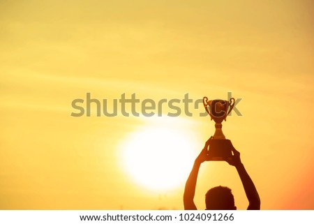 Winner holding golden trophy cup.Silhouette Best Award victory trophy for professional champion challenge Man holding trophy cup over head success in goal. Win-Win Business Concept. #1024091266