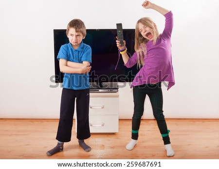 Winner in the fighting over the remote control - Sister is happy with it but her brother is very upset.