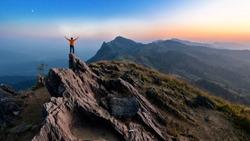 Winner man on peak of rocks mountain Hike at sunset, Active life concept