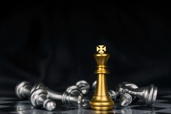 Winner. shot of golden king surrounded with silver chess pieces on chess board game competition with dark background, chess battle, victory, success, team leader, teamwork, business strategy concept