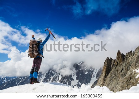 Winner / Success concept. Hiker cheering elated and blissful with arm raised in the sky after hiking to mountain top summit above the clouds