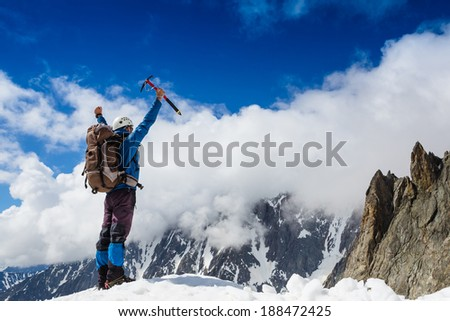 Winner Success concept Hiker cheering elated and blissful with arms raised in the sky after hiking to mountain top summit above the clouds