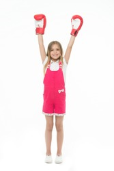 Winner takes it all. Girl on smiling face posing with boxing gloves as winner, isolated white background. Kid long hair celebrates victory. Girls power concept. Child ambitious likes win and success.