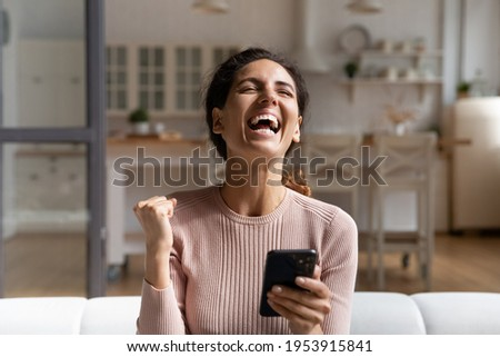 Winner time. Overjoyed young latina female sit on sofa alone hold phone laugh raise up fist proud with victory in game lottery online. Happy excited woman celebrate success scream yes full of emotions