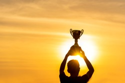 Winner win holding golden champion trophy cup prize. Silhouette best award victory trophy for professional champion challenge team holding gold sport trophy cup over head. Win-Win sport team concept