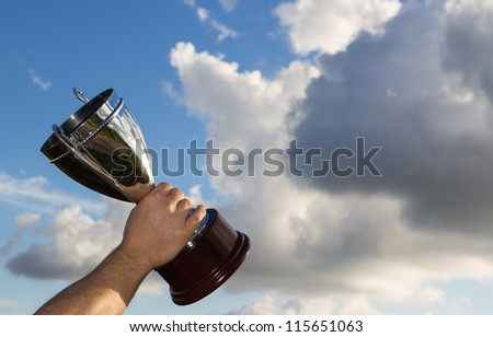 Winner with cup in hand to the sky