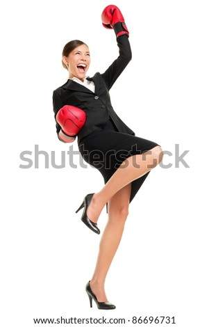 Winning business woman celebrating wearing boxing gloves and business suit. Winner and business success concept photo of young multiracial Asian Caucasian businesswoman isolated on white background. - stock photo