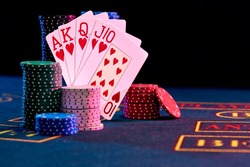 Winning combination in poker standing leaning on multicolored chips piles on blue cover of playing table. Black background. Casino concept. Close-up.