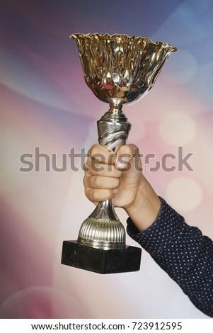Winning cup in hand. Symbol of success, winning, championship #723912595